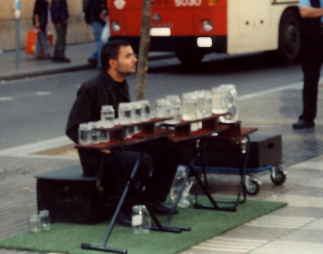 Busker playing a water-jar xylophone
