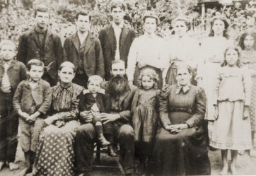 Mr Solomon Shelton, with beard, is seated in the front row holding a young boy.  Virginia Shelton is standing at the extreme right on the front row.  Donna Shelton is the girl standing on the back row next to the tall man